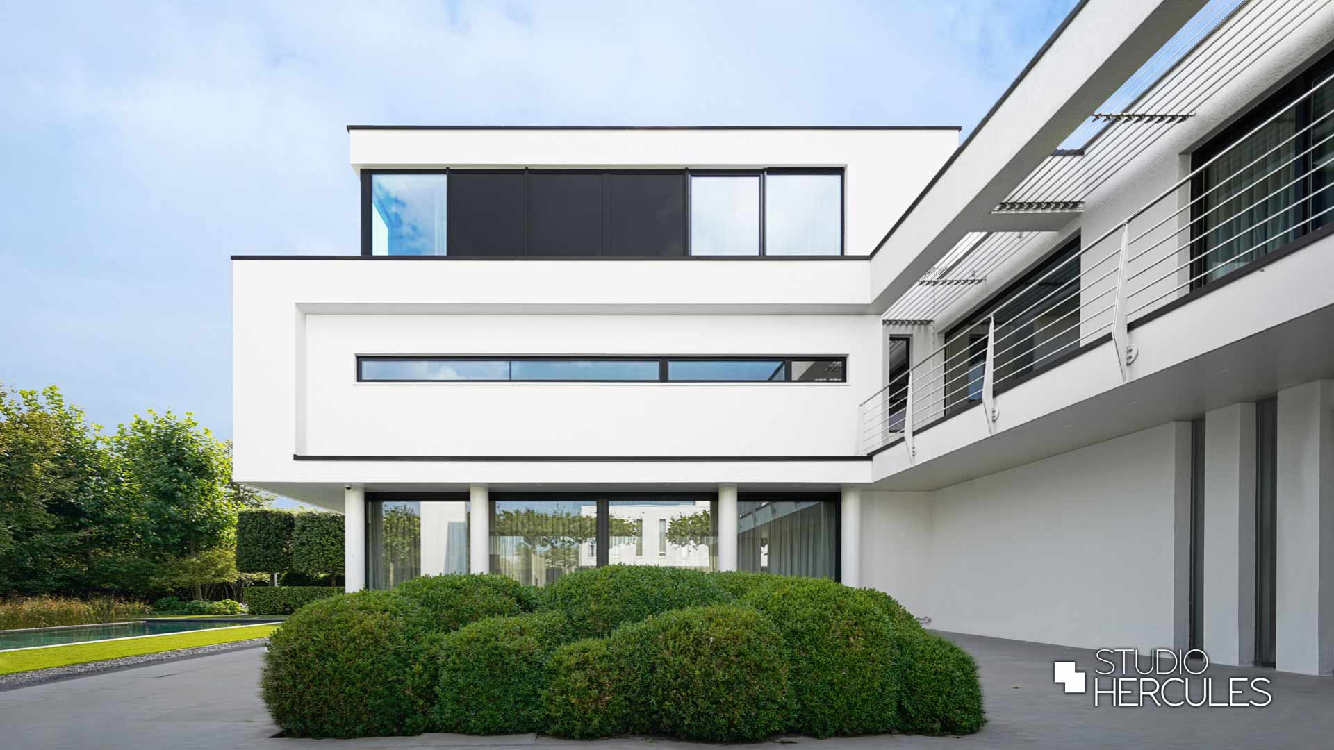 Zijgevel met langwerpig raam en granieten tuinelementen.